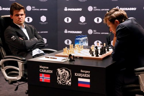 Magnus Carlsen, of Norway, sits while Sergey Karjakin, of Russia, looks at the chess board during their opening match in the 2016 World Chess Championship in New York